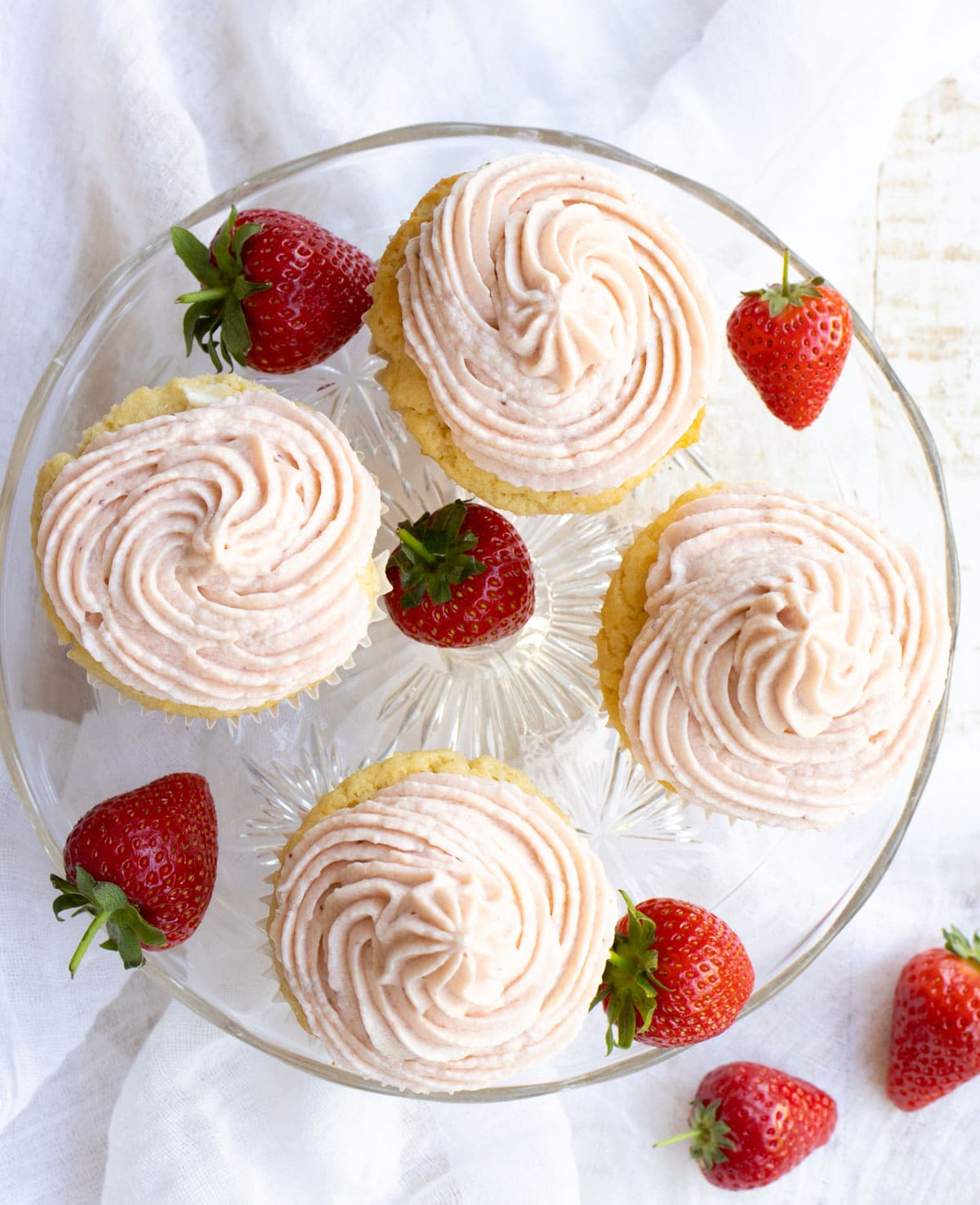 4 cupcakes with strawberry buttercream frosting on a cake stand with strawberries