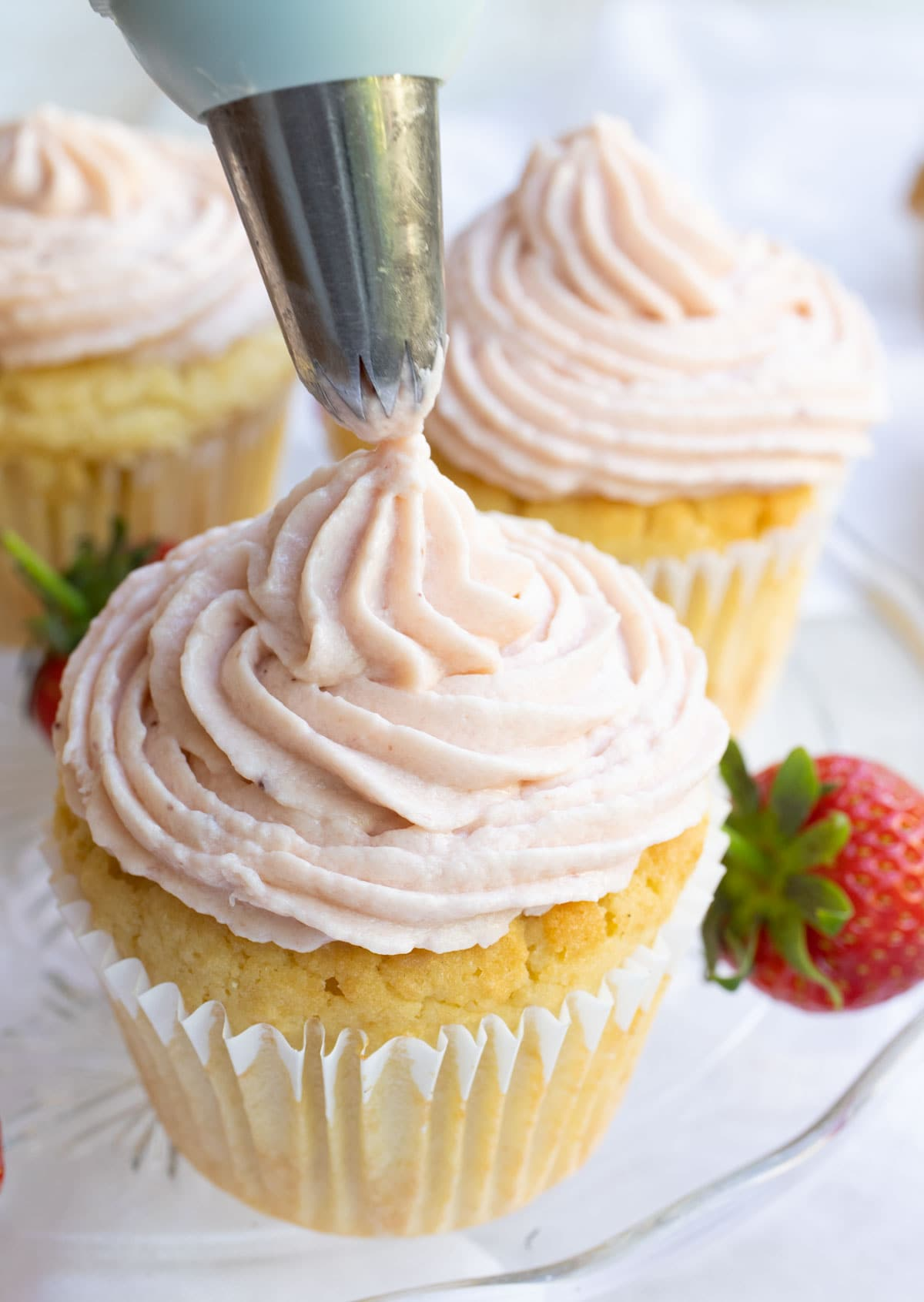 piping keto strawberry frosting onto a cupcake