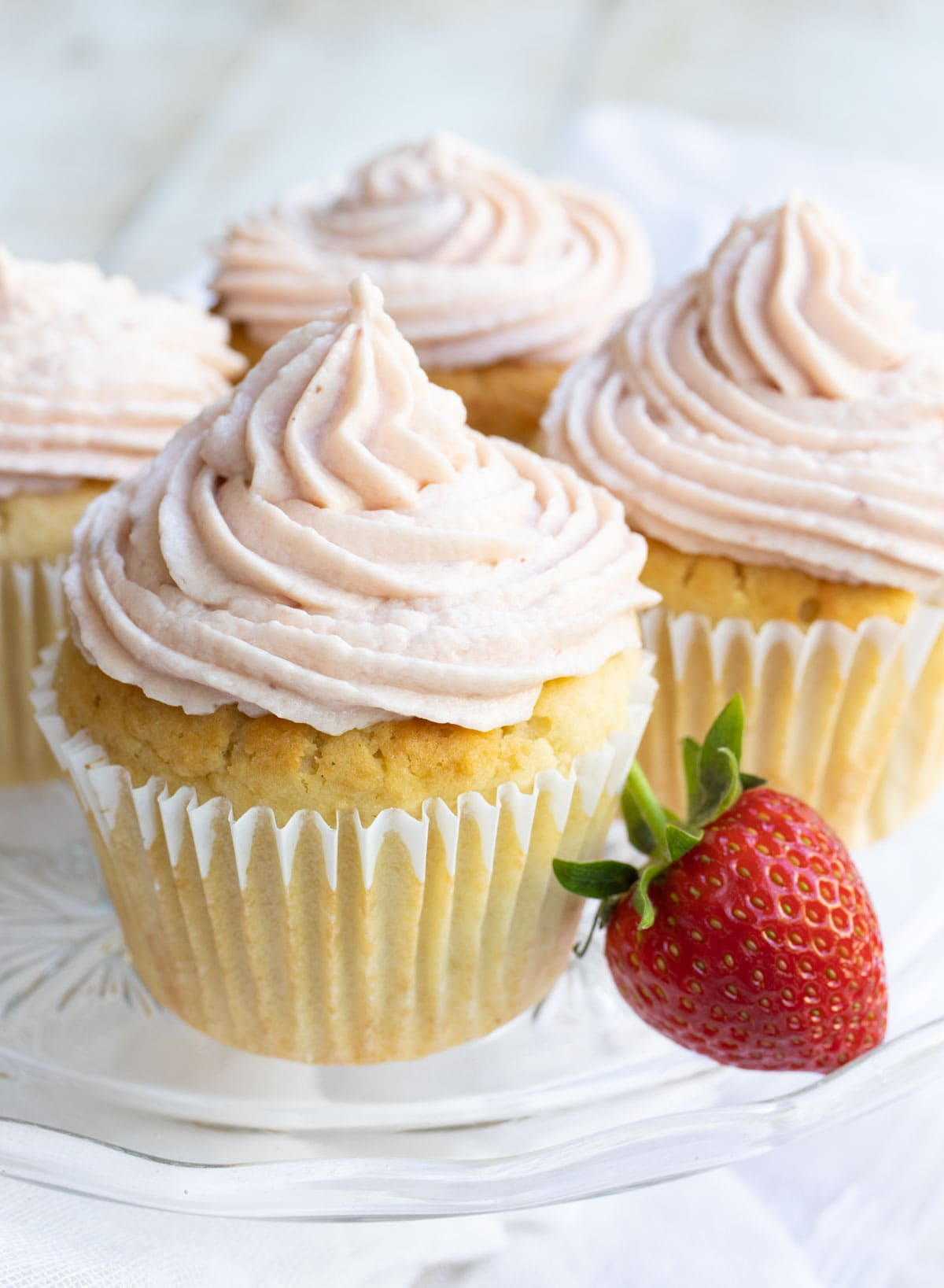 keto cupcakes with strawberry frosting and a strawberry on the side