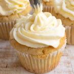 topping off a keto vanilla cupcake with cream cheese frosting