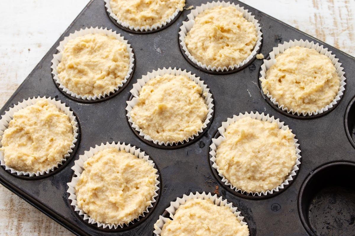 cupcake batter in paper cups in a cupcake pan