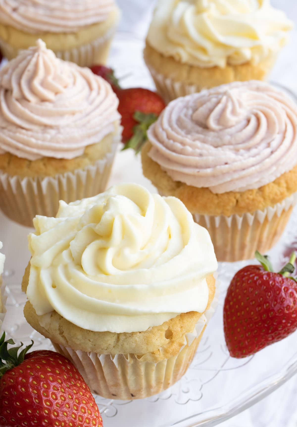 cupcakes with vanilla and strawberry frosting and strawberries on a cake stand