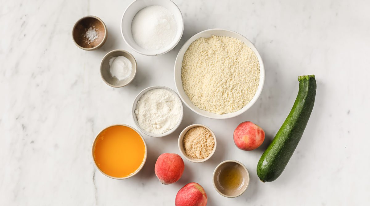 peaches, zucchini and other ingredients measured into bowls