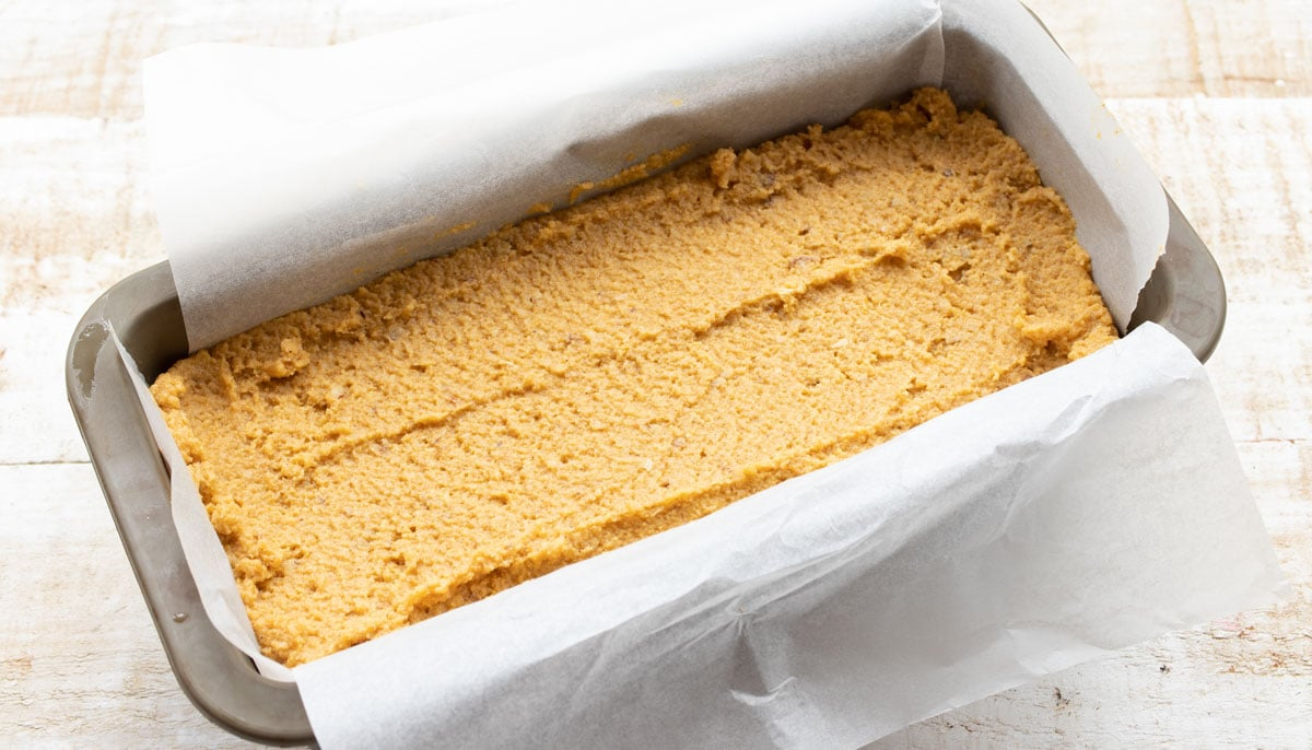 batter in a parchment paper lined loaf tin