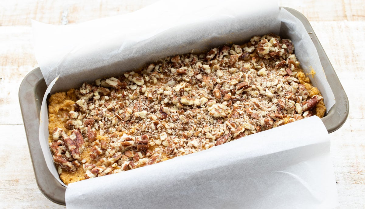 adding chopped pecans on top of the batter in a loaf tin