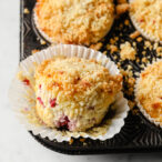 closeup of a keto raspberry muffin released from its paper cup