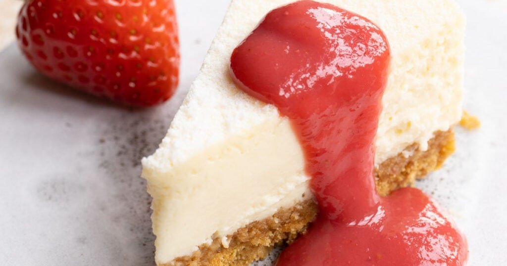 strawberry sauce on a cheesecake slice