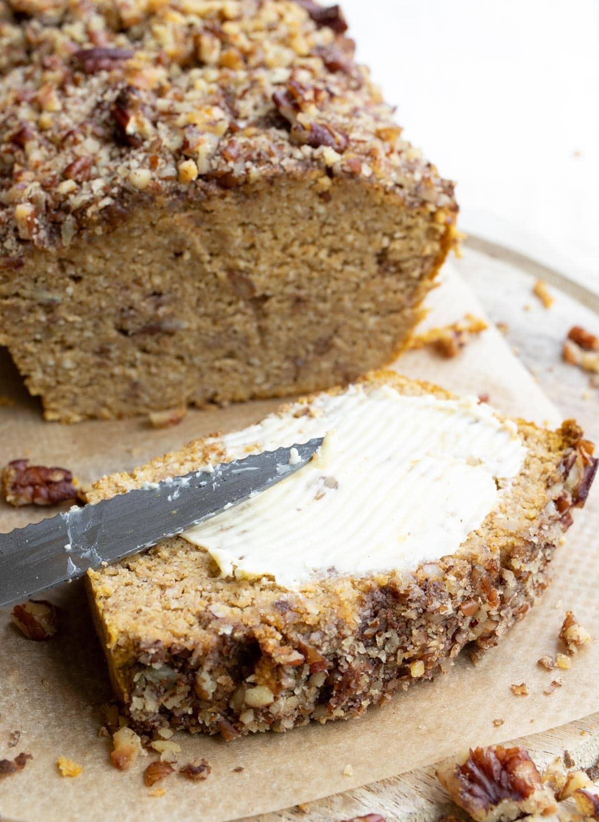 spreading butter onto a slice of pumpkin bread