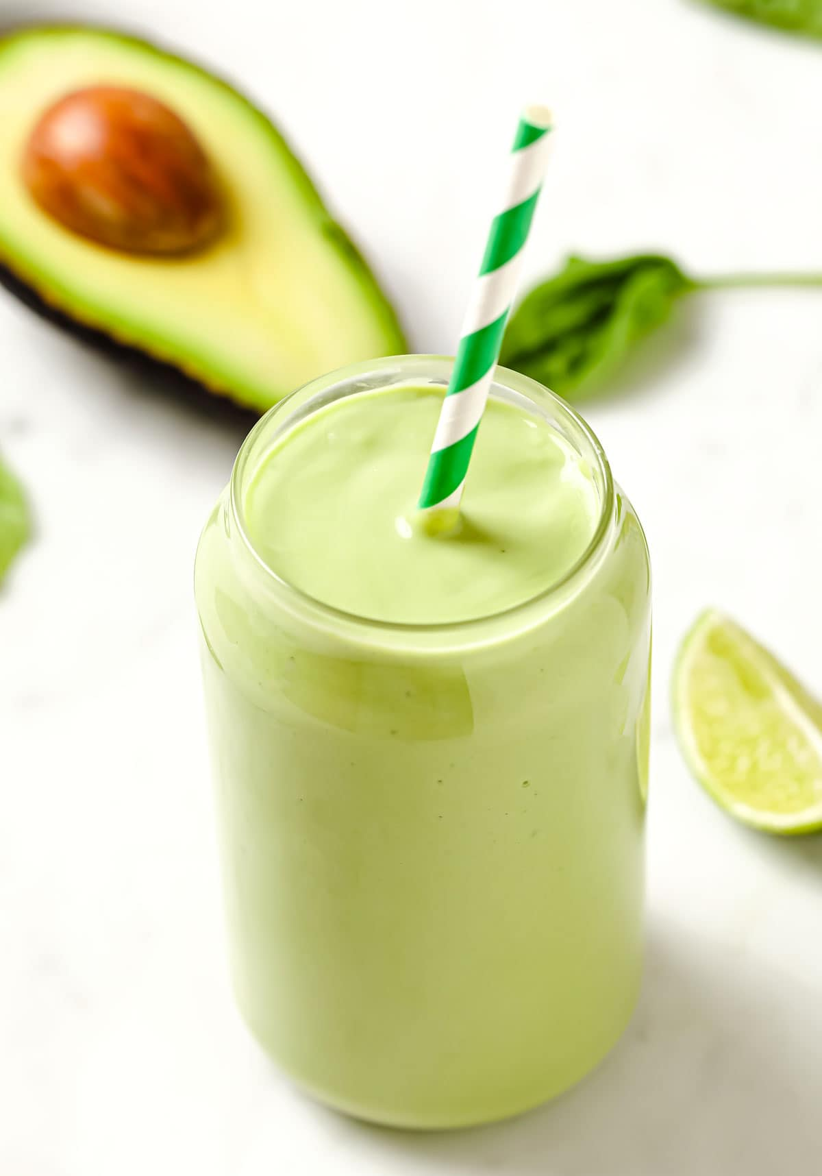 a glass with avocado smoothie and a straw