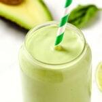 closeup of a keto avocado smoothie with a green straw