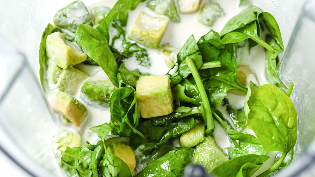 spinach, avocado cubes and nut milk in a blender cup