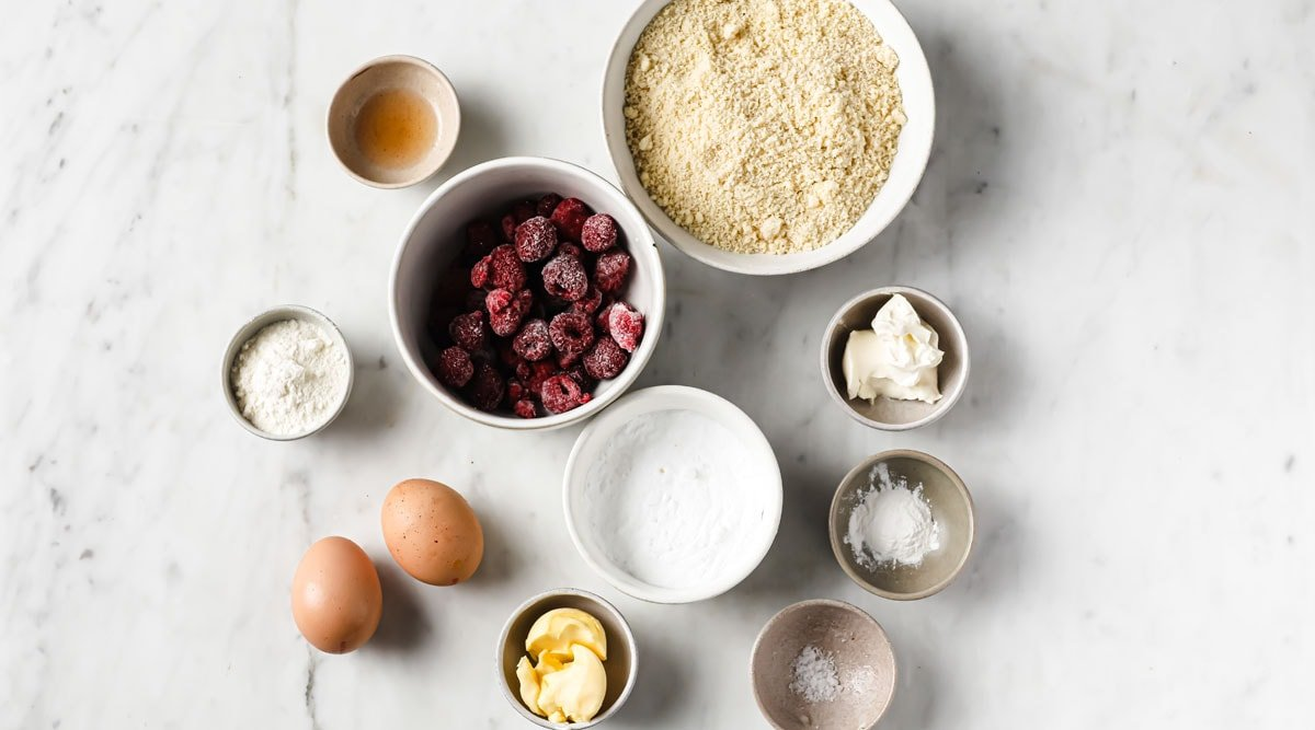 ingredients such as frozen raspberries, almond flour and eggs measured into bowls and