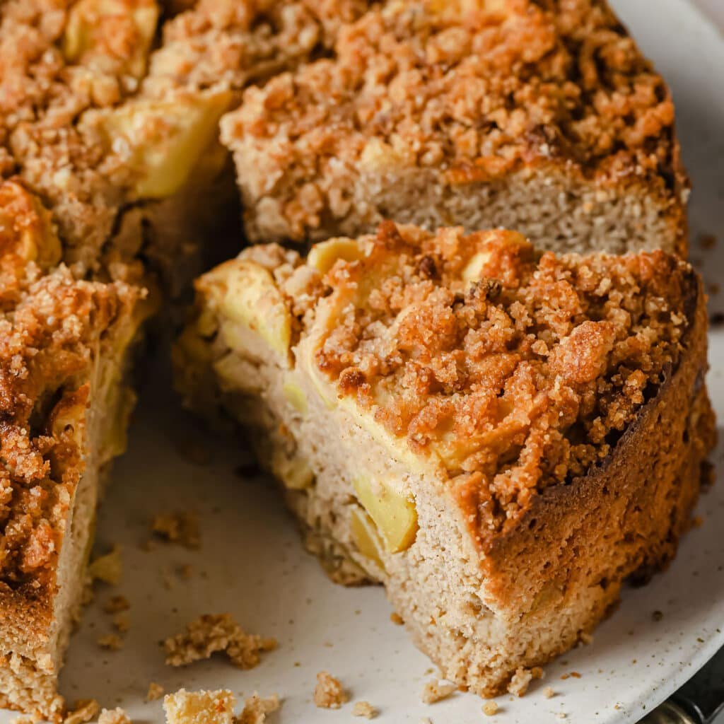 a keto apple cake sliced with apple pieces inside and streusel topping