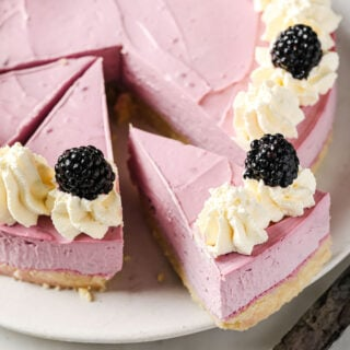 sliced keto blackberry cheesecake decorated with whipped cream rosettes and topped with fresh blackberries