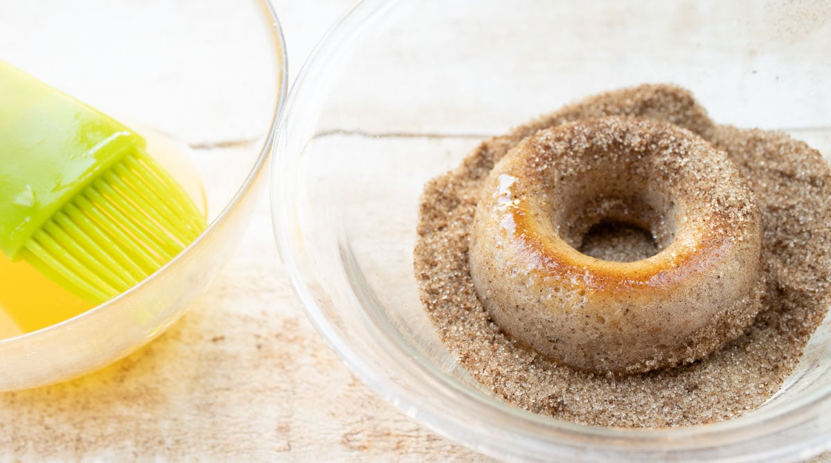 a bowl with cinnamon sweetener mix and a donut being coated