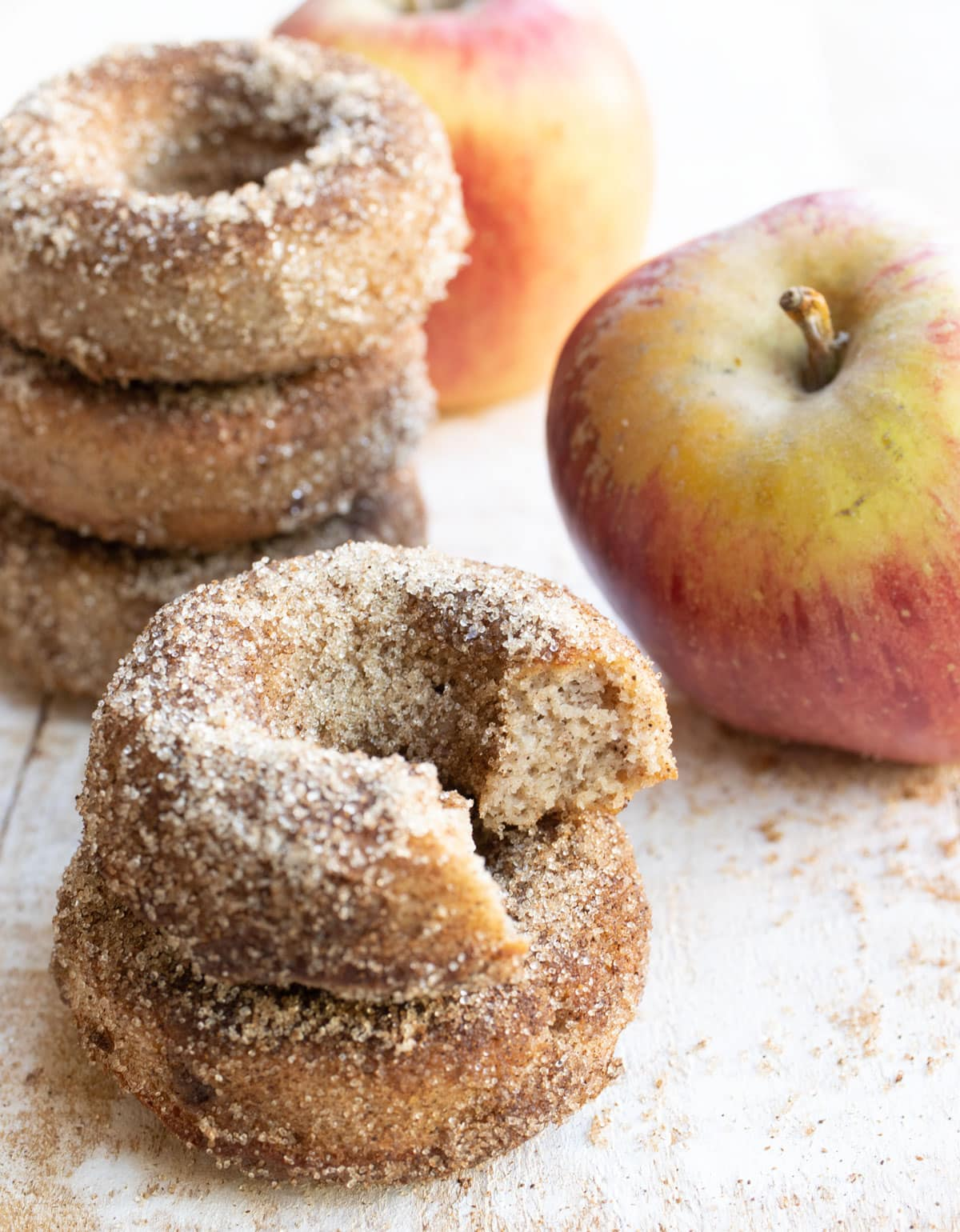 stacked donuts, one is bitten into and apples in the background